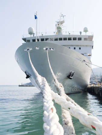 Berthing ropes on a pier with the big ship Stock Photo