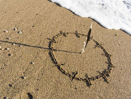 Sundial are drawn on wet sea sand