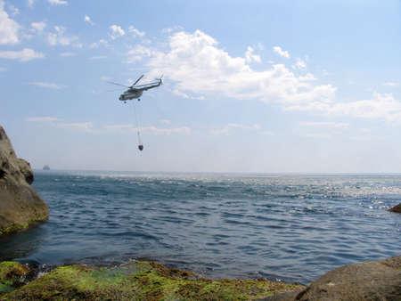 retardant: elicottero raccoglie l'acqua dal mare nel serbatoio per la soppressione di incendi boschivi