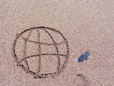Figure of globe on wet sea sand Stock Photo