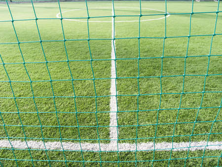 Field for game in football with a green grass and white lines a kind through a grid photo