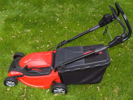 Lawnmower standing on grass Stock Photo
