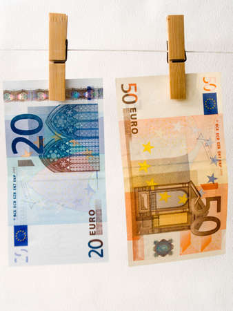 Euro of a banknote on a cord for linen with clothespins photo