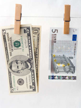Euro of a banknote and dollars on a cord for linen with clothespins photo