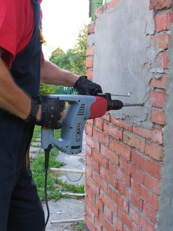 Working male jackhammer destroy the old Foundation, red brick Stock Photo