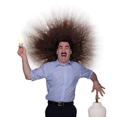 electrifying: Electrocuted long haired man changing a lightbulb Stock Photo
