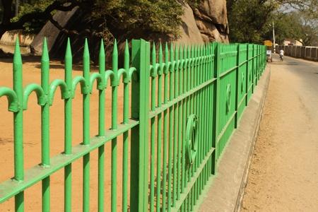 rejas de hierro: valla verde entre el parque y la carretera