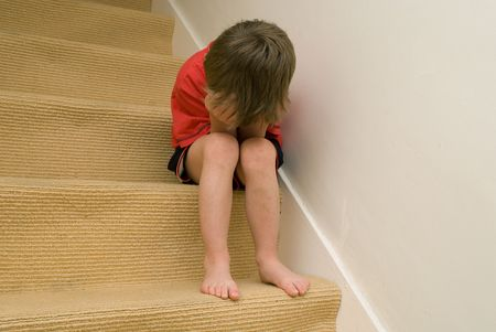 fear child: Upset Child sitting on stairs with his head in his hands.
