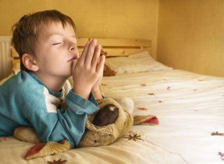 Little boy praying at bedtime. Stock Photo