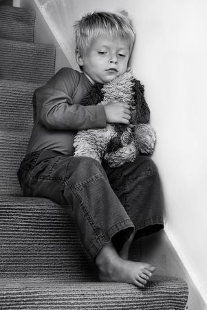 Young Child sitting on the stairs looking troubled.  photo