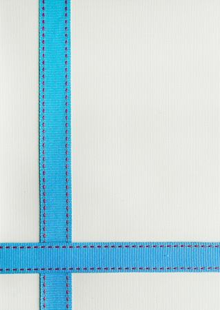 lineas horizontales: Cinta azul con costura rojo sobre un fondo de textura.