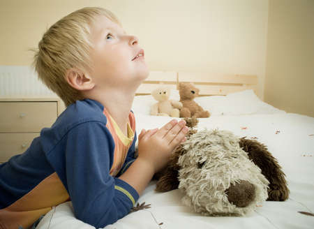 Little boy prays in the bedroom by the bed. Stock Photo