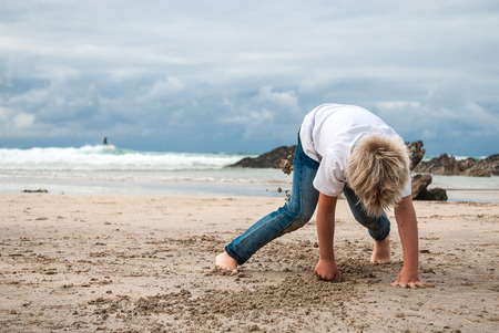 Child playing in sand on the beach Stock Photo