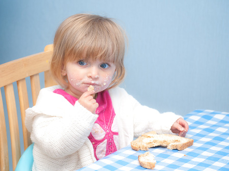 A little girl aged around 18 months eating bread and butter  Stock Photo