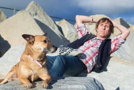 A man relaxing outdoors with his dog on the beach, selective focus used on the dog