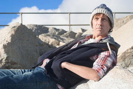 A casual man sitting outdoors, wearing warm clothing with a serious expression
