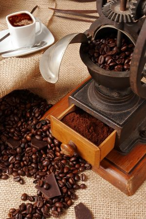 Grinder with coffee beans and a cup of expresso photo
