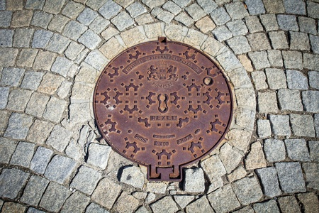 Budapest rusted sewer cap surrounded by pavement granite stones