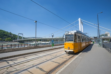 elisabeth: Yellow tram on the river bank of Danube in Budapest and Elisabeth Bridge, Hungary Stock Photo