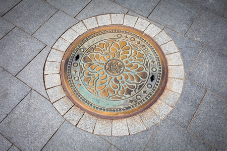 Budapest rusted sewer cap surrounded by pavement granite stones photo