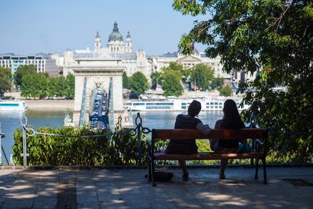 szechenyi: BUDAPEST, HUNGR�A - 02 de agosto: Dos muchachas en un banco mirando al Puente de las Cadenas Szechenyi el 2 de agosto de 2013 en Budapest. Foto de archivo