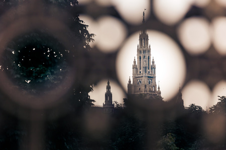 Gothic building tower of Vienna city hall, Rathause, seen trogh a fence, Austria photo