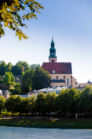 Hallstatt, Austria - August 5, 2013: Pfarramt Mulln catholic church, overseeing the historical old town in Salzburg, Austria. photo