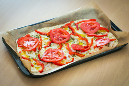 Delicious fresh traditional Italian focaccia bread with tomatoes, red peppers, onions, basil and olive oil on pan ready to cook photo