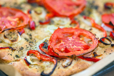 Delicious fresh traditional Italian focaccia bread with tomatoes, red peppers, onions, basil and olive oil on cooking pan photo