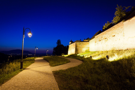 cetatuia: Alley arround old  fortress Cetatuia illuminated at night, Brasov, Romania