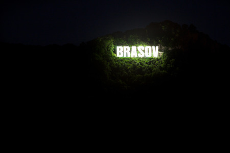 Brasov city sign on top of Tampa mountain illuminated at night, Romania photo