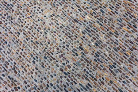 cobblestone street: Seamless tile background made of small stones (pebbles) on sidewalk or wall