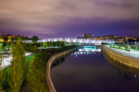 rio: Madrid, Spain - May 8, 2012: Arganzuela Bridge illuminated on a spring night and Madrid Rio Park, Madrid, Spain