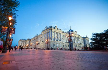 palacio: Madrid, Spain - May 10, 2012: Royal palace (Palacio Real de Madrid) with visiting tourists on a spring night in Madrid, Spain