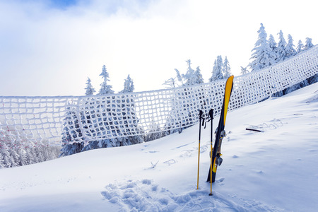 Ski equipment on ski run with pine forest covered in snow seen trough a frozen fence on back in winter season - Poiana Brasov photo