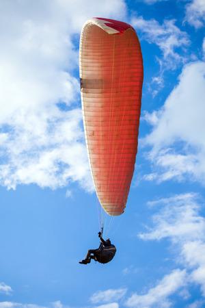 paraglider: Paraglider flying on blue sky