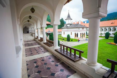 colonade: Sambata, Romania - June 24, 2012: Church inside Sambata de Sus Monastery seen trough a colonade in Transylvania, Romania