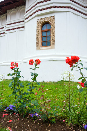 Flowers in front of Sambata de Sus Church inside Monastery courtyard in Transylvania, Romania Stock Photo