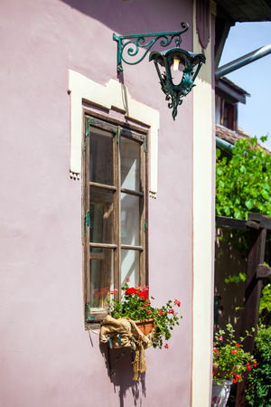 turda:  Pink facade with white windows and street lamp on an old pink house from the Sighisoara city old center, Romania Stock Photo
