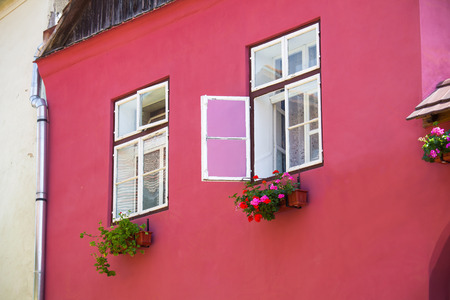 turda:  Pink facade with white windows and street lamp on an old pink house from the Old Turda city center, Romania Stock Photo