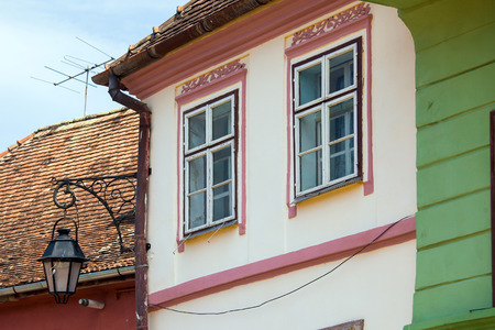 Pink facade with white windows and street lamp on an old pink house from the Old Turda city center, Romania photo