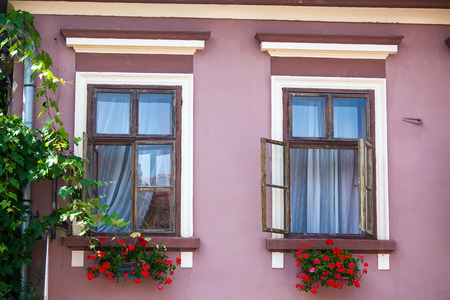 old center: Sighisoara, Romania - June 23, 2013: Pink facade with windows and flowers from Sighisoara city old center, Transylvania, Romania Stock Photo