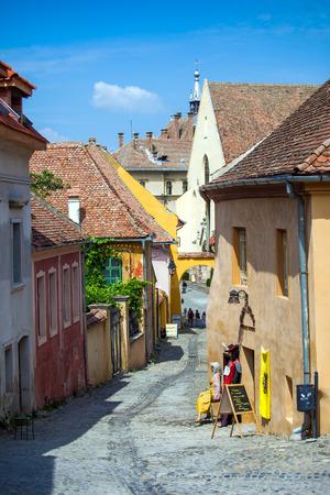 turda: Sighisoara, Romania - June 23, 2013: Old stone paved street with tourists from Sighisoara fortress, Transylvania, Romania Editorial