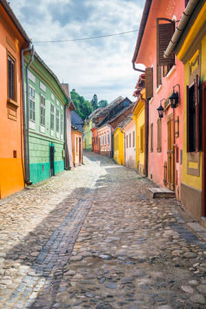 Sighisoara Romania  June 23 2013: Stone paved old streets with colored houses from Sighisoara fortresss Transylvania Romania