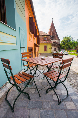Sighisoara Romania  June 23 2013: Table with chairs on stone paved old street and colored houses from Sighisoara fortresss Romania
