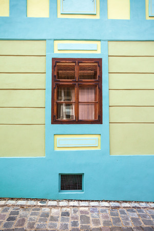 old center: Sighisoara Romania  June 23 2013: Blue house facade with wooden window from Sighisoara city old center Transylvania Romania