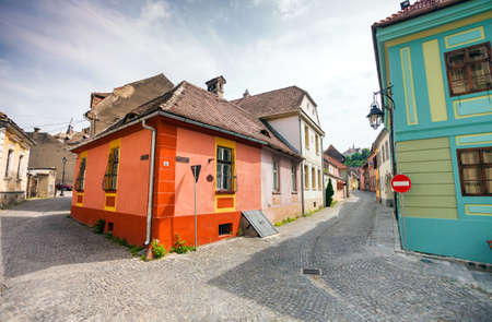 turda: Sighisoara Romania  June 23 2013: Stone paved old streets with colored houses from Sighisoara fortresss Transylvania Romania