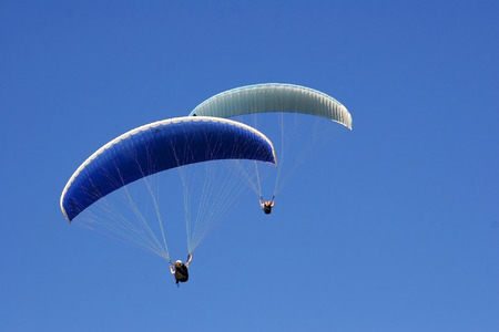 Paraglider soaring in a blue sky Stock Photo