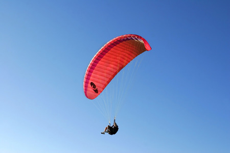 high powered: Paraglider soaring in a blue sky Stock Photo