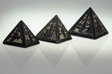 tremendous: three stone pyramids with hieroglyphs standing in line and refracting in surface
